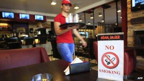 A waitress walks past a No Smoking sign in a cafe in Beirut on 3 September 2012