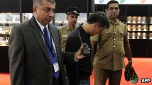 A Sri Lankan security official (L) and uniformed police escort a Chinese national (C) who is accused of stealing a $13,800 diamond by swallowing it