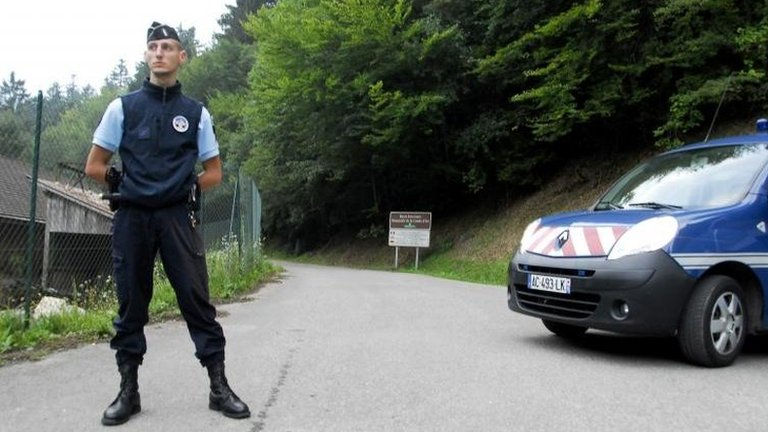 A French gendarme blocks the road leading to the scene where four people died in a shooting at a parking near the Annecy Lake, eastern France, on Wednesday
