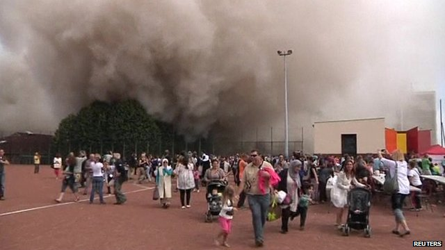People flee dust cloud after building demolition