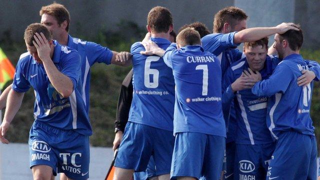 Ballinamallard players celebrate the late winner against Cliftonville