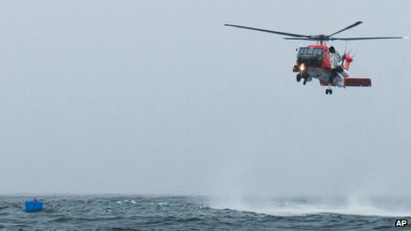 A photo taken from a nearby vessel shows the Coast Guard helicopter as it rescued Harris, below left