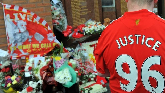 Floral tributes and man wearing shirt reading 'Justice 96'