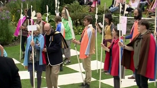 People in The Prisoner costumes playing human chess
