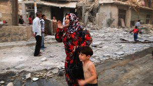 Woman and child running through street after air strike in Aleppo, Syria