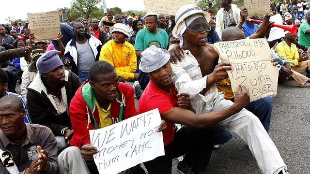 Miners hold placards as police stop them from proceeding with their march in Rustenburg, South Africa