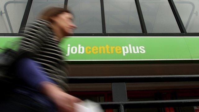 A woman walking past a Job Centre Plus