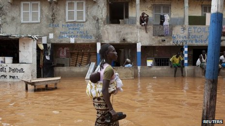 A woman with a baby on her back wades through water after overnight flooding on a street in Senegal's capital Dakar, 14 August 2012