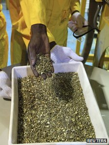 A worker holds gold pieces during the inauguration of the Sudan Gold Refinery in Khartoum on 19 September 2012