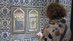 A member of the media takes notes beside a ceramic tile display in the Louvre's new Islamic art wing, 20 September