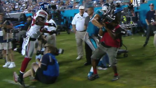 Antrel Rolle and Greg Olsen collide with two cameramen
