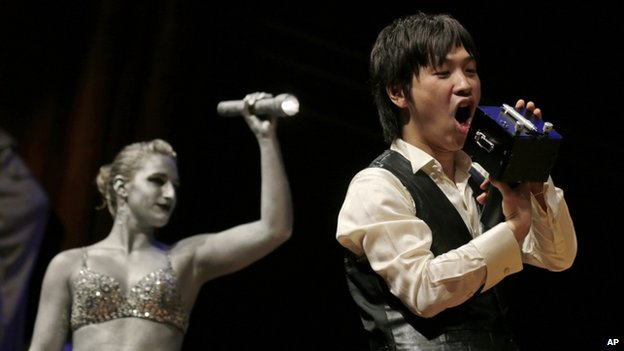 """Koji Tsukada yells into his invention the """"SpeechJammer"""" during a performance at the Ig Nobel Prize ceremony"""