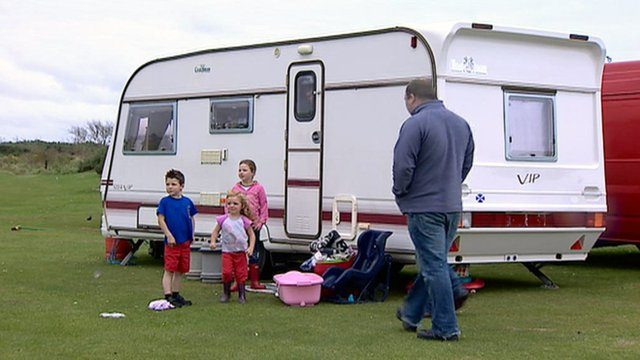 Family standing outside their caravan