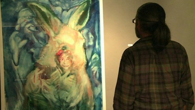 A man looking at one of the paintings on display