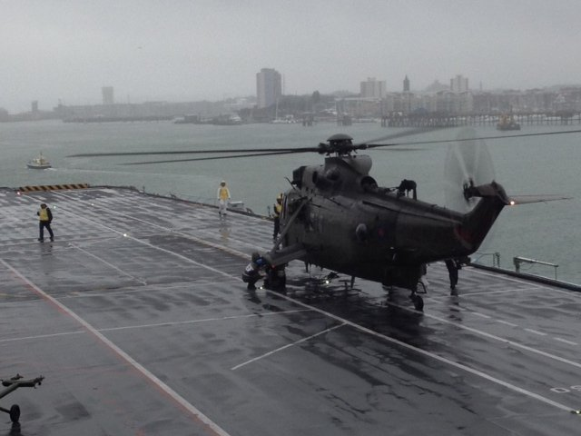 Sea King helicopter lands on HMS Illustrious before its departure
