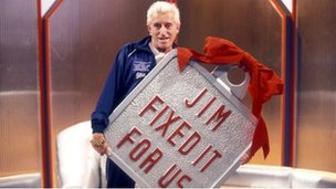 Jimmy Savile with giant Jim Fixed It For Us Badge