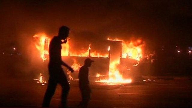 Men walking past burnt out bus