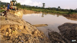 A boy sits beside the pit where miners died when the roof of an illegal gold mine collapsed at Dunkwa on-Offin in central Ghana (27 June 2010)
