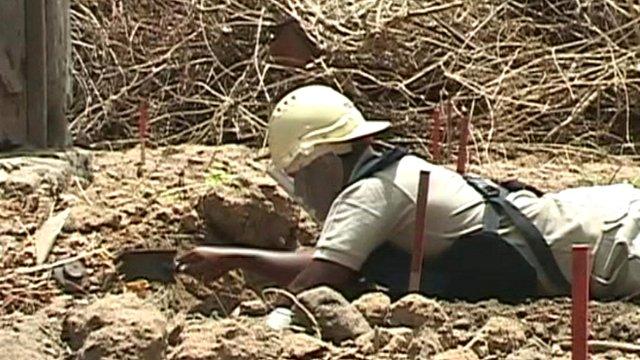 Woman digs around a landmine