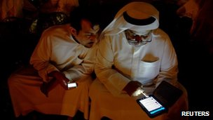 Kuwaitis check their messages at a sit-down protest in Kuwait City, 19 October