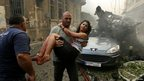 A wounded woman is carried at the site of the blast in Beirut. Photo: 19 October 2012