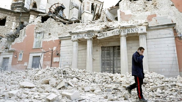 Italian military carabinieri walks on debris past destroyed buildings after an earthquake
