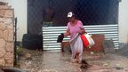 Woman wades through flood water