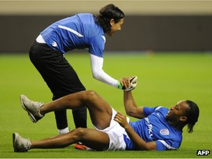 Didier Drogba helped up by Shanghai Shenhua goalkeeper Dong Guangxiang