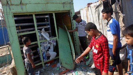 Iraqis inspect the site of a bomb attack at Al-Bawiya market, in the east Baghdad district of Maamal