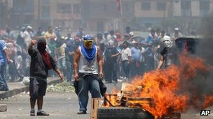 People create burning road blocks to protest against attempts to relocate vendors from La Parada Market to another area in Lima, Peru, 27 October 2012