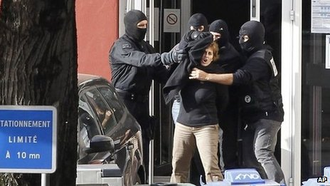 Izaskun Lesaka, centre, surrounded by French Police officers, reacts as she leaves the hotel where she was arrested in the early hours of October 28