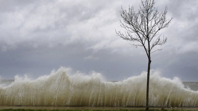 Waves come over sea wall on Long Island, New York