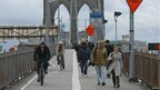 Commuters walk across the Brooklyn Bridge into lower Manhattan after the subway was flooded. Photo: 31 October 2012