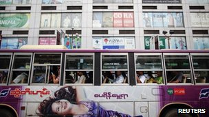 Passengers wait for a bus to leave a station in front of a shopping mall in central Yangon