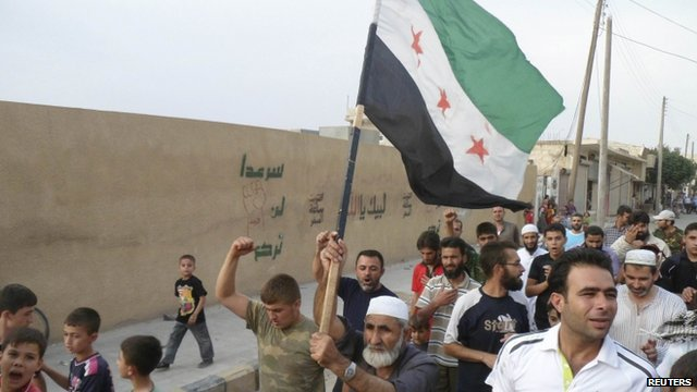 Residents hold an opposition flag during a protest against Syria's President Assad in Sermada