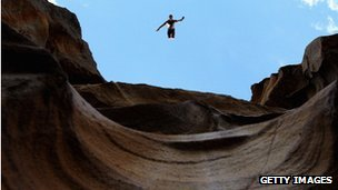 diver jumping off a cliff edge