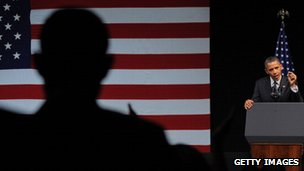 President Obama giving a speech with US flag behind him