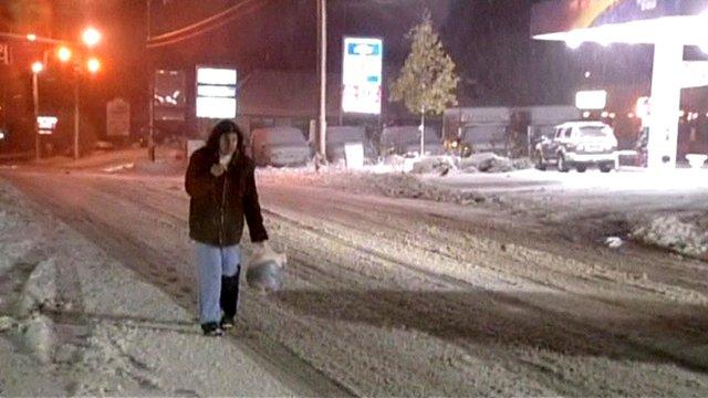 Woman walking in snowy street