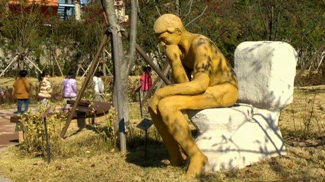 Sculpture of man on toilet