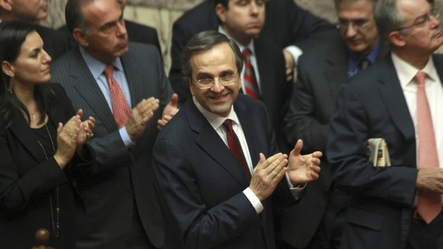 "Greece""s Prime Minister Antonis Samaras and his party's lawmakers of the New Democracy party applaud after voting on the country's 2013 budget"