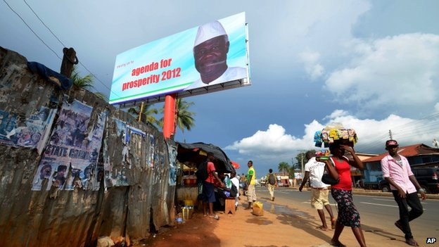 People walk past a campaign poster for incumbent President Ernest Bai Koroma, in Freetown, Sierra Leone, Friday, Oct. 19, 2012.