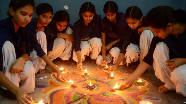 """Indian school girls lighting candles as they sit near a """"Rangoli"""", which is made out of coloured powder during pre Diwali celebration at a school in Amritsar"""