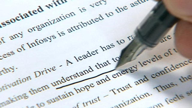Man uses pen to underline text on paper