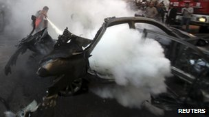 A man extinguishes the fire in a car targeted by an Israeli air strike in Gaza City