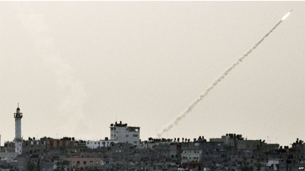 A missile and its vapour trail streak across the sky above Gaza City