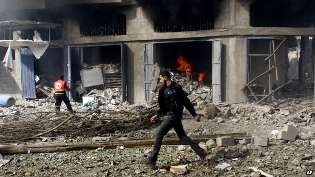 Man walks past rubble