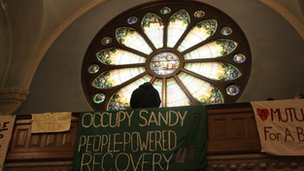 "Stained glass window and banners that say ""Occupy Sandy: People Powered Recovery"