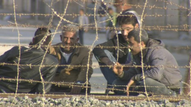 Men sitting by fence