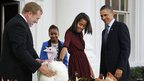 "President Barack Obama and daughters Malia, front, and Sasha, rear, ""pardon"" a Thanksgiving turkey"