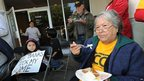 Julia Botello, 84, eats the Thanksgiving meal with homeowners facing eviction outside a bank in Long Beach, California